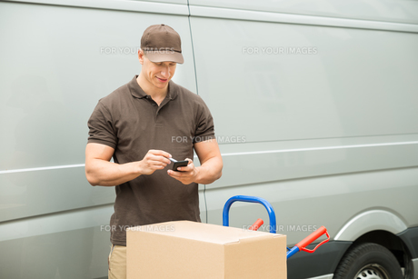Delivery Man Checking List On Mobile Phoneの写真素材 [FYI00761070]