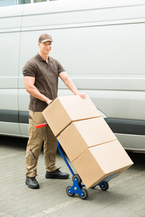Delivery Man Holding Trolley With Cardboard Boxesの写真素材 [FYI00761073]