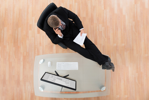 Businessman Reading Document In Officeの写真素材 [FYI00761075]