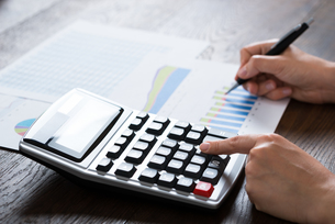 Businesswoman Analyzing Financial Report With Calculatorの写真素材 [FYI00761076]