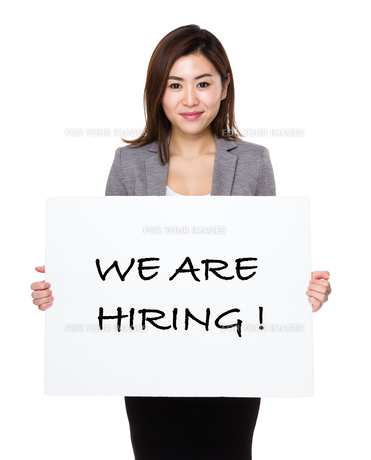 Young businesswoman holding a poster showing with we are hiring phrasesの写真素材 [FYI00761941]