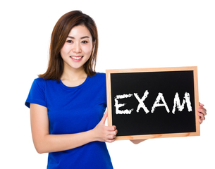 Young woman with blackboard showing a word examの写真素材 [FYI00761967]