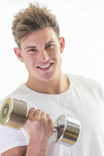 Smiling young man with gym weightsの素材 [FYI00762566]