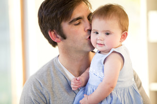 Father kissing his baby daughter on the cheekの写真素材 [FYI00762571]