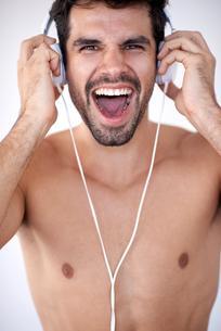 handsome young man listening music on headphonesの写真素材 [FYI00762980]