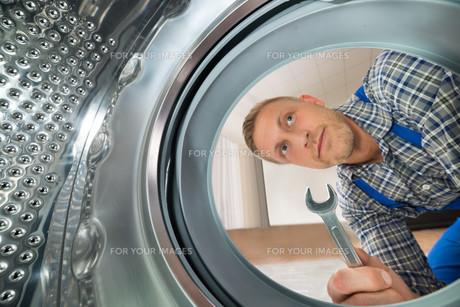 Repairman Looking Inside The Washing Machineの写真素材 [FYI00763041]