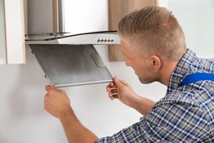 Repairman Repairing Kitchen Extractor Filterの写真素材 [FYI00763043]