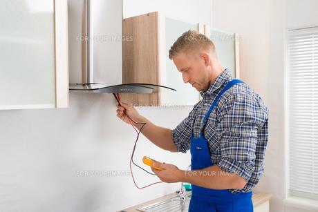 Worker Testing Kitchen Hood With Multimeterの写真素材 [FYI00763045]