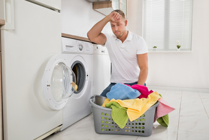 Tired Man Loading Clothes Into The Washing Machineの写真素材 [FYI00763046]