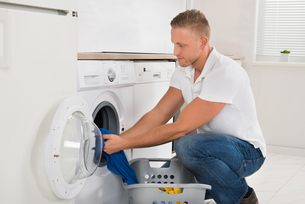 Man Loading Washing Machine With Clothesの写真素材 [FYI00763057]