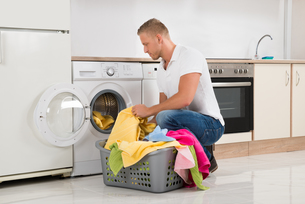 Man Putting Dirty Clothes Into The Washing Machineの写真素材 [FYI00763058]