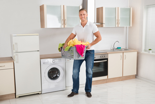 Man Carrying Laundry Basket In Kitchen Roomの写真素材 [FYI00763061]