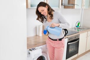 Woman Pouring Liquid Detergent In The Bottle Capの写真素材 [FYI00763108]