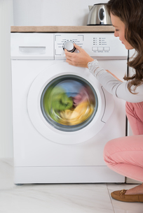 Woman Pressing Button Of Washing Machineの写真素材 [FYI00763117]