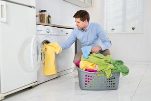 Man Loading Clothes Into Washing Machineの写真素材 [FYI00763230]