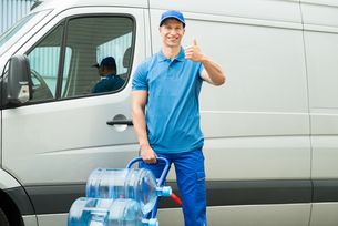 Delivery Man Holding Trolley With Water Bottlesの写真素材 [FYI00763251]