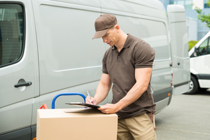 Delivery Man Writing On Clipboardの写真素材 [FYI00763257]