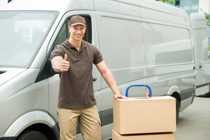 Delivery Man With Cardboard Boxes Showing Thumbs Up Signの写真素材 [FYI00763261]