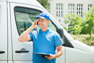 Worker In Front Of Truck Writing On Clipboardの写真素材 [FYI00763272]