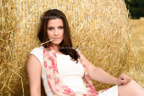 Young Caucasian woman with long brown hair leaning against a bale of strawの写真素材 [FYI00763435]