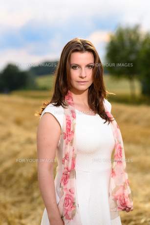 Young woman in white dress standing in a fresh mown corn fieldの写真素材 [FYI00763440]