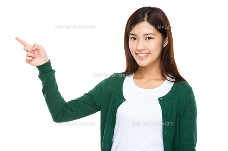 Smiling woman pointing away, copy space conceptの写真素材 [FYI00763534]