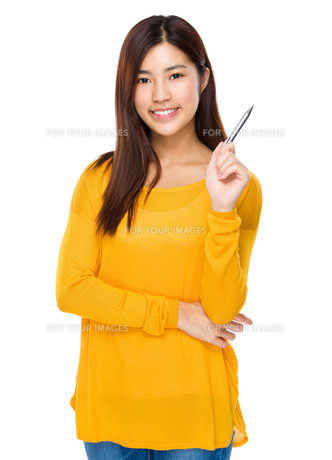 Asian woman with pen pointing upの写真素材 [FYI00763589]
