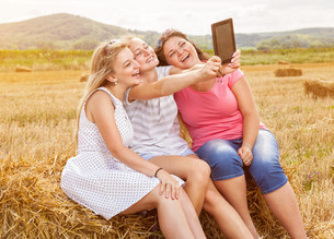 Group of friends in a field taking a picture with a tabletの写真素材 [FYI00763620]