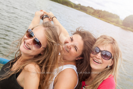 Group of friends having fun outdoors on a lakeの写真素材 [FYI00763629]