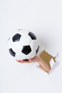 Hand break through paper with soccer ballの写真素材 [FYI00763700]