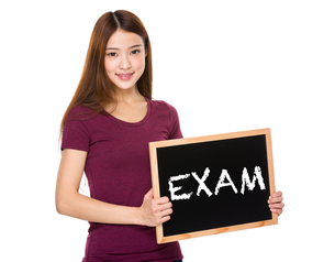 Young student hold with chalkboard showing a word examの写真素材 [FYI00763750]