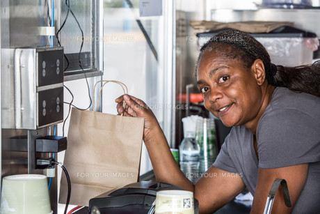 Smiling African-American Worker Hands Food Order Out Windowの素材 [FYI00764272]