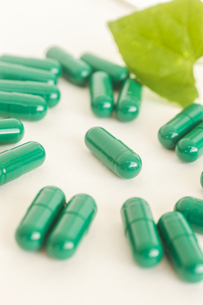 Herb in green capsule spilling on white backgroundの写真素材 [FYI00764728]
