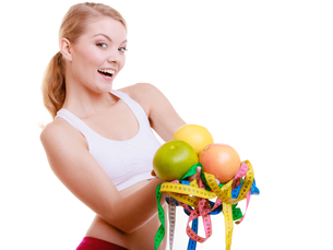 sports fit woman with measure tapes fruits. time for slimming diets.の写真素材 [FYI00764987]