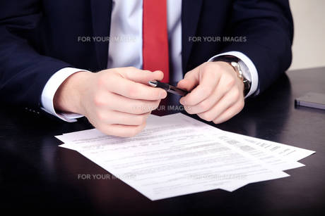 Close-up of male hands with pen over documentの写真素材 [FYI00765316]
