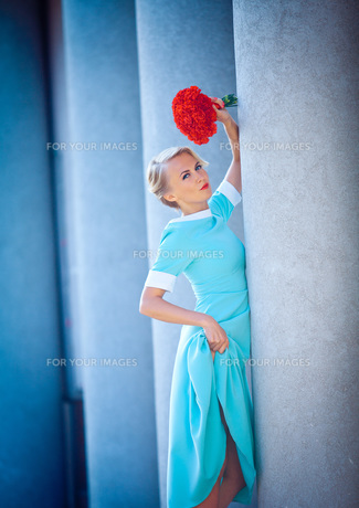 The girl in a blue dress with red flowers in a town near a large stone columnsの写真素材 [FYI00765346]