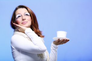 winter makeup woman with cup of hot bevergeの写真素材 [FYI00765384]