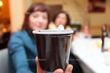 woman's hand with plastic brown cup of coffeeの素材 [FYI00765498]