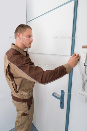 Carpenter Taking Measurement Of Doorの写真素材 [FYI00765542]