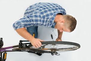 Man Fixing Bicycle Wheelの素材 [FYI00765543]