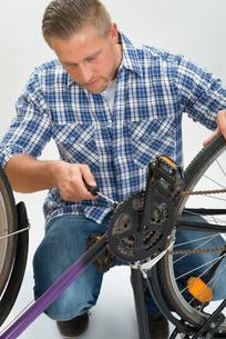 Young Man Fixing Bicycleの素材 [FYI00765553]