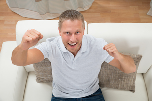 Man Clenching Fist On Sofaの写真素材 [FYI00765562]