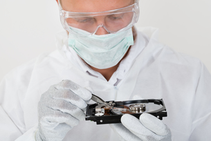 Man Repairing Harddisk With Tweezersの写真素材 [FYI00765567]