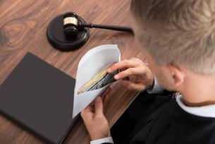 Judge Looking At Money In Courtroomの写真素材 [FYI00765579]