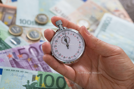 Person Hands With Stopwatch Over Moneyの写真素材 [FYI00765606]