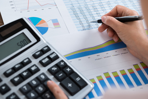 Businesswoman Analyzing Financial Report With Calculatorの写真素材 [FYI00765620]