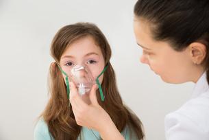 Doctor Holding Inhaler Mask For Girl Breathingの写真素材 [FYI00765626]