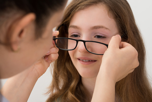 Optician Putting Eyeglasses On A Patientの写真素材 [FYI00765633]