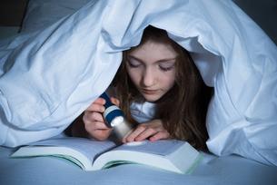 Girl Reading Book With Flashlightの写真素材 [FYI00765656]