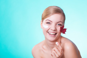 skin care. face of young woman girl with red maple leaf.の写真素材 [FYI00765661]